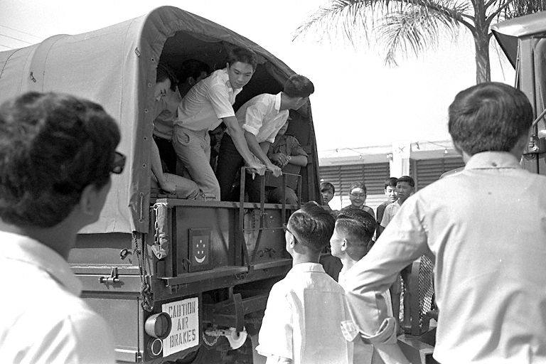 National Service recruits boarding a military truck at Pek Kio Community Centre during their enlistment day.
