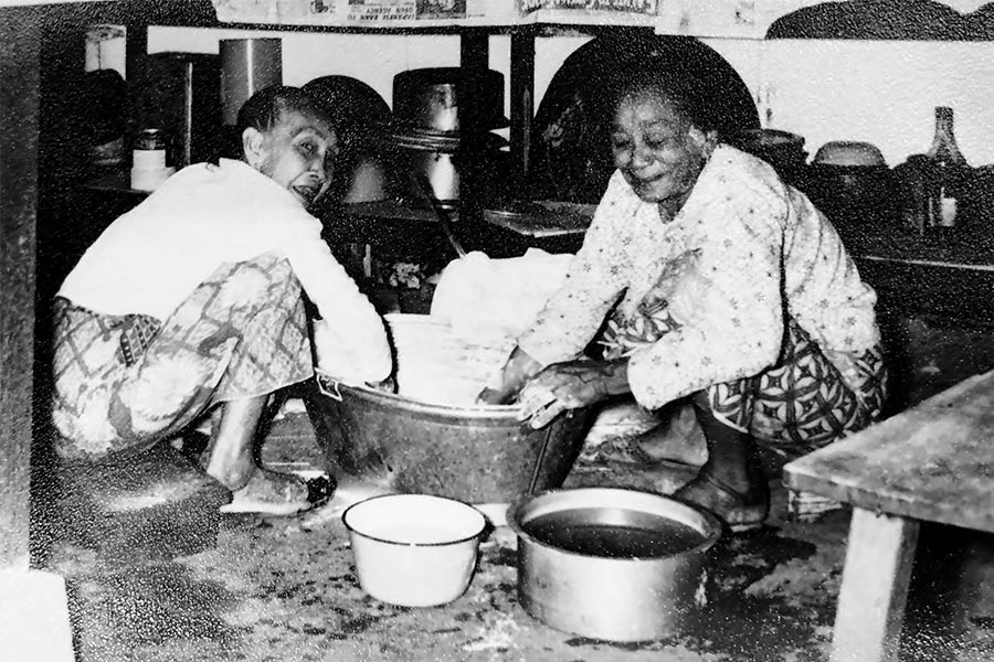 Photograph of Papathy Pillay and a relative in the kitchen at their Kampong Batak Residence